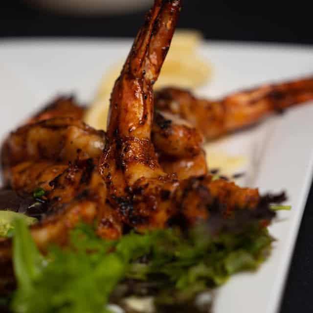 Grilled shrimp over lettuce appetizer with lemon slices