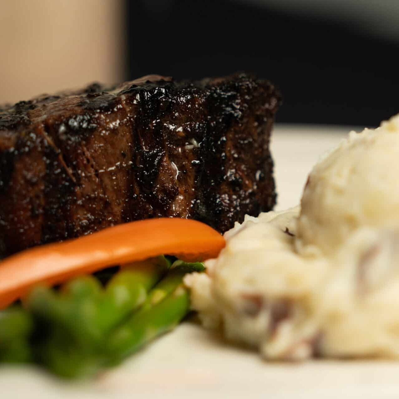 Juicy steak with grill marks, fresh vegetables, and fluffy mashed potatoes