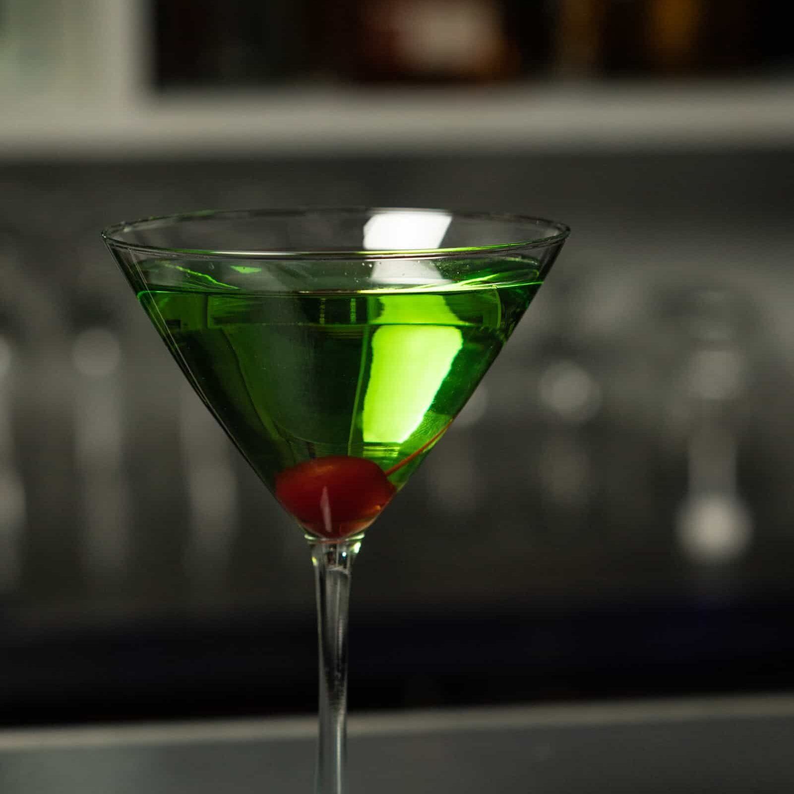 Green alcoholic cocktail in a cocktail glass with a cherry in the bottom
