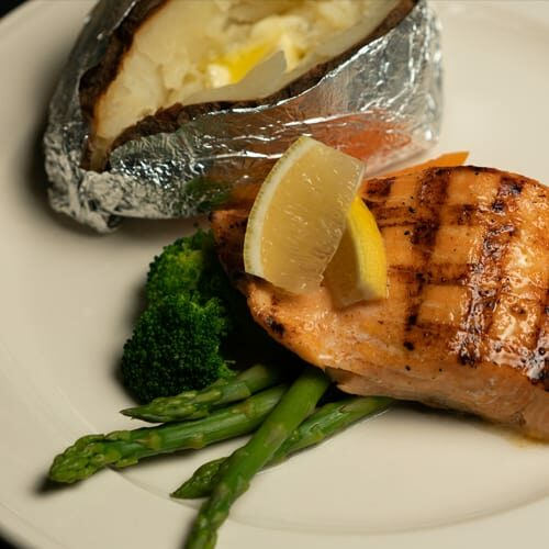 Grilled tender Salmon topped with lemon sided with fresh Asparagus and a crispy Baked Potato